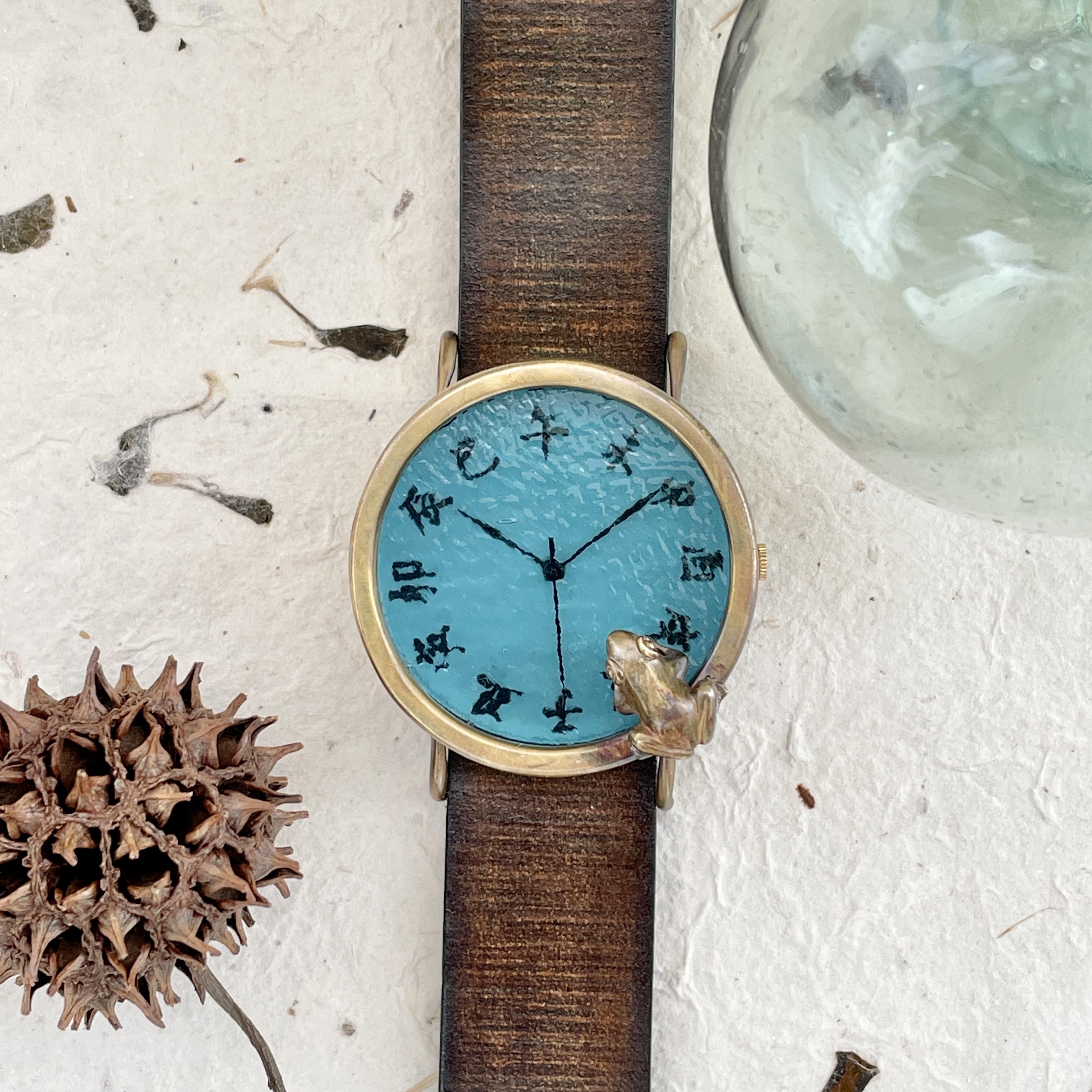 池をのぞく蛙腕時計L渋青緑