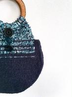 籐の持ち手のネイビーとブルー、ベージュ、グリーンのミックス糸で編んだ楕円のトート
