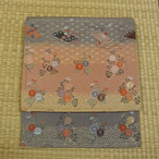 ピンクとグレーのぼかしに巻物と花 袋帯