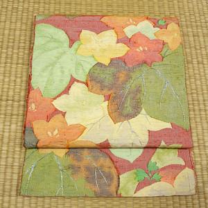 朱色に大柄の花と葉 開き名古屋帯