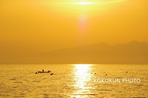 朝日の中漁をする風景
