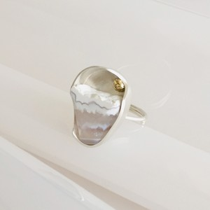 一点モノ 丸い入れ物の中の貝殻と雲の国か雪の国の指飾り