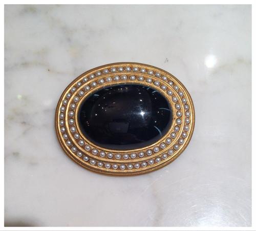 黒の樹脂に金彩、パールがグルリと巻いているブローチ