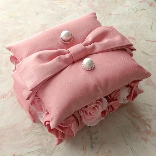 間にとも布のバラを飾ったピンクのリングピロー