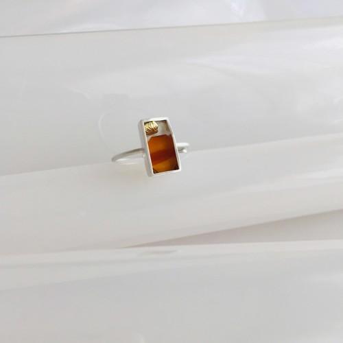 一点モノ 入れ物中の貝殻とオレンジ色の波の小さな石の指飾り