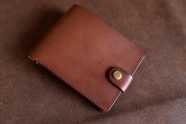 シンプルな二つ折りの茶色い牛革の財布