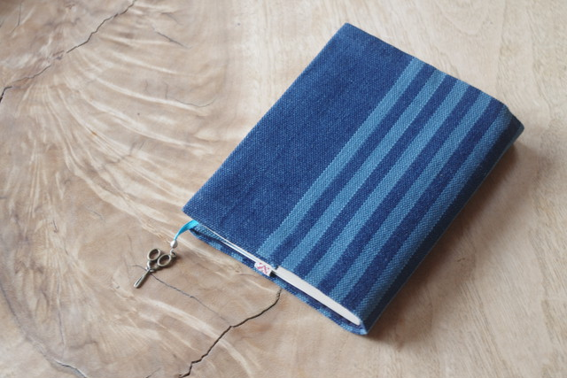 出かけるときには本を一冊持って行く、という方に。落ち着いた藍色ストライプ サイズ調整ができる、しおりが付いた文庫本サイズのブックカバー(栞の先にハサミ型のチャーム付き)