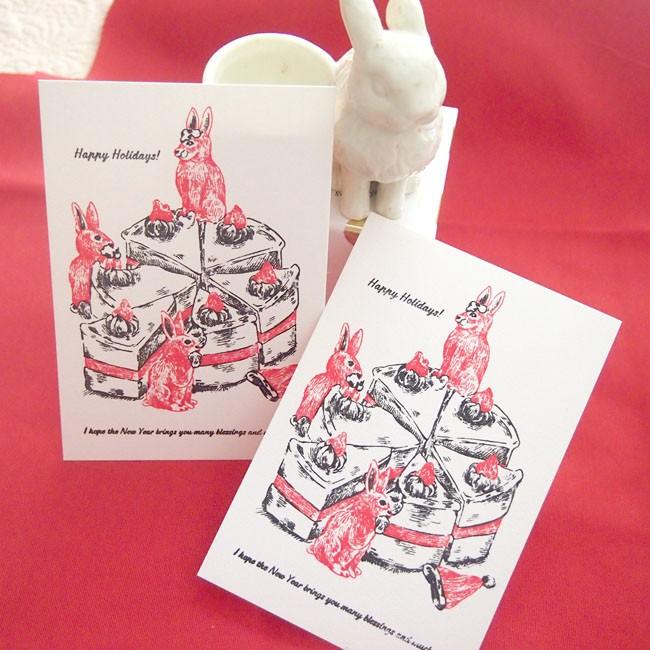 ホールのケーキをカットする楽しい瞬間。3匹のうさぎとホールのケーキのカード。
