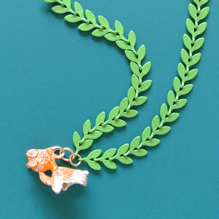緑葉のチェーンが印象的な金魚のネックレス。尾びれのゆらめきにもこだわって作られました。