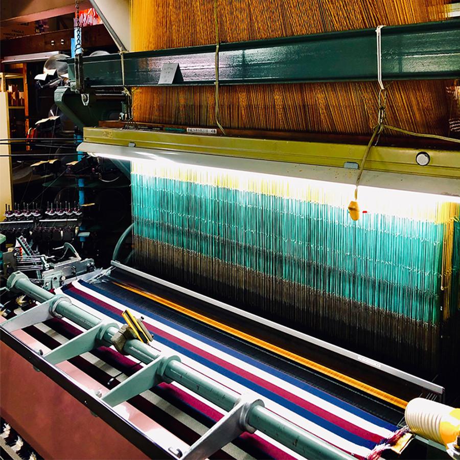 昔ながらの紋紙を使って織る織機です、織り上がった生地は手前で巻かれていきます